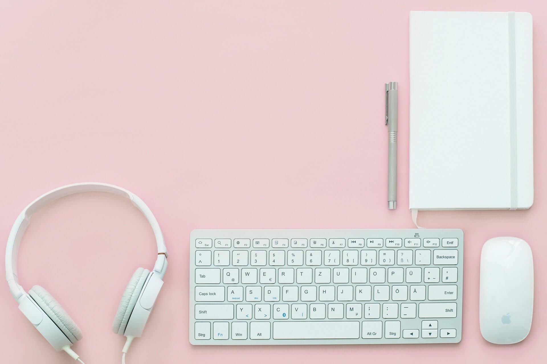 casque audio souris et clavier apple et carnet avec stylo